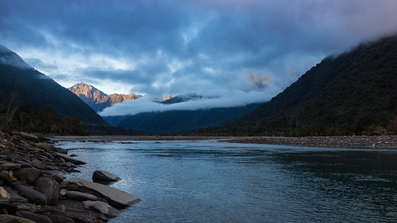 Parting clouds reveal Mt Hawkins above a moody Mahitahi.