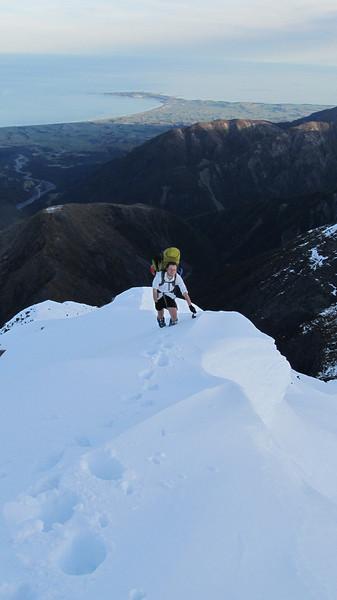 Step plugging high on Surveyor Spur, Kaikoura peninsula below.