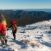 Reaching the summit of Mt Richmond in a strong southerly. Arthur Range in the distance.