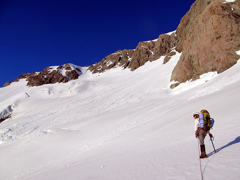 The route up the Freshfield Glacier to the Grand Plateau goes up the steep snow slope between the rocks centre image.
