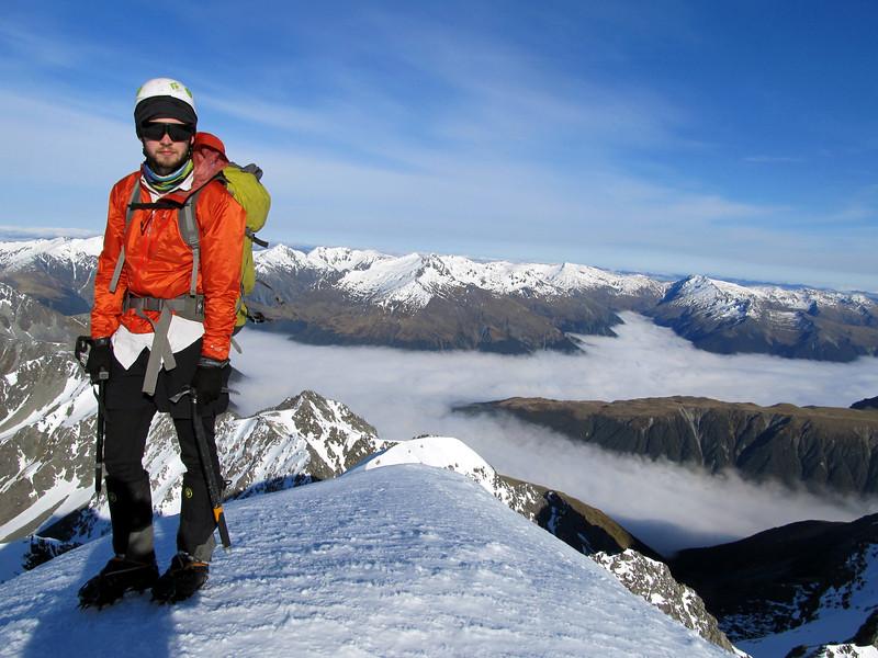 James on the summit of Mt Una, Matakitaki valley below in cloud.