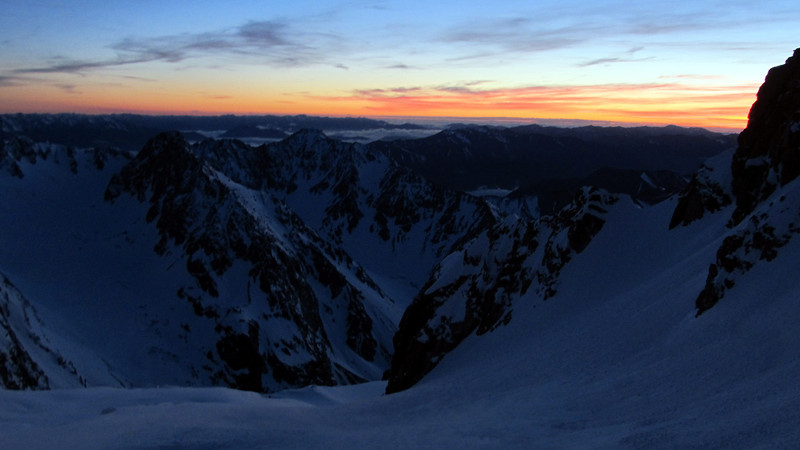Sunrise at the schrund at the bottom of the central couloir of Arrowsmith, Marquee in the centre image.