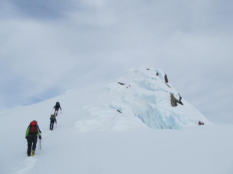 Just below the summit of the low peak.