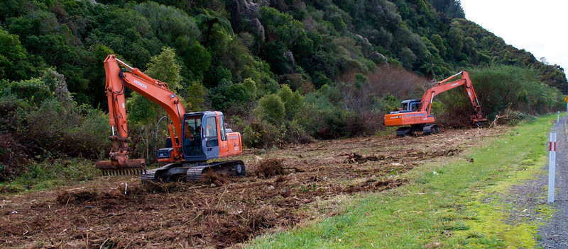 Diggers working on River Road, Upper Hutt Jun 2010.<br /> <br /> Diggers working clearing scrub in preparation to widen the road to add a wire rope median barrier.