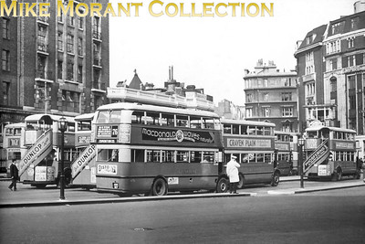 "An interesting one for the London bus aficionados. This is the bus stand outside London's Victoria station and it seems that the picture, a lantern side by the way, couldn't have been taken in any year other than 1934. When the LPTB was formed on July 1st 1933 it briefly adopted ""General"" as its bus brand name. The London Transport fleet name didn't come into general use until well into 1934 and buses were still being delivered from Chiswick with the GeneraL name until well after this photo' was taken. Some acquired buses, notably but not exclusively from the Tilling Group, were actually repainted by the LPTB into this ""General"" livery which was ironic as LGOC and Tilling had been bitter rivals. STL 277, the bus nearest the photographer with licence plate AUC 517, was completed at Chiswick works when it's body was mounted on 30th November 1933 and it was licensed and entered service with effect from 1st December so this photo could not have been taken any earlier than that. However, this type of STL was an LGOC design which was inherited by the LPTB and it continued in production until late in 1934, by which time 405 bodies of the same basic type had been completed. In the interim, the (now) LPTB design team at Chiswick had been cleaning up the design and the first of these bodies were completed in October 1934. These STLs were the last large batch of buses delivered to the LGOC/LPTB with petrol engines, and subsequent batches had the ubiquitous AEC 7.7 litre oil engine, a specification to which the majority of petrol engined STL buses (including STL 277) were converted. STL 277 later operated from Forest Gate (G), Willesden (AC), Chalk Farm (CF) and Cricklewood (W) garages and was withdrawn from service wef 17th October 1950 and sold to R L Daniels of Rainham in Essex for scrapping. [Mike Morant collection]"