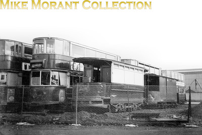 London trams LT tramcars await their collective fate at the famous Penhall Road scrapyard in Charlton. At the right of the shot is The now redundant Thornton Heath/Purley snowbroom 034 awaiting its fate with the others at Penhall Road yard, Charlton. At its last repaint this snowbroom was beautifully turned out and was kept so.   It carried its original passenger car classification of CLASS B on its rocker panels. Interestingly, the last snowbroom in service in 1952 was Holloway's 037 which too was similarly treated but carried CLASS C due to its different builder. Behind 034 is another of the works fleet - a Class J stores van. [Mike Morant collection]