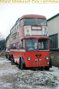 London Transport C2 class trolleybus no. 260 stored alongside Smith's garage at Whitley near Reading in February 1963. What looks like snow was so compacted that the whole area visible here was solid ice. [Slide taken by Mike Morant]