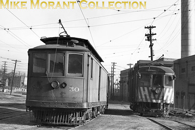 Des Moines RailwayCar 50, builder and date unknown, and Des Moines & Central Iowa Railway  car 71, 1913 McGuire-Cummings built line cars operated for the inter-related companies, near the freight house in Des Moines, Iowa in 1948.CAPTION TEXT KINDLY SUPPLIED BY CLIFF SCHOLES.