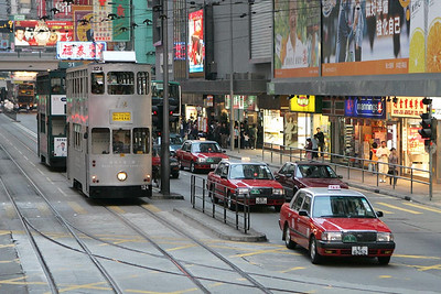 No 124 heads westwards along Hennessy Road, Causeway Bay with a service for Whitty Street Depot on 21/11/2004. The line coming in from the right is the single track loop around the Happy Valley racecourse.