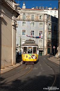 554 works an E12 service to Praça da Figueira as it runs downhill along Largo da Sé outside the Lisbon Cathedral, or Church of Santa Maria Maggiore, on 22/11/2016.