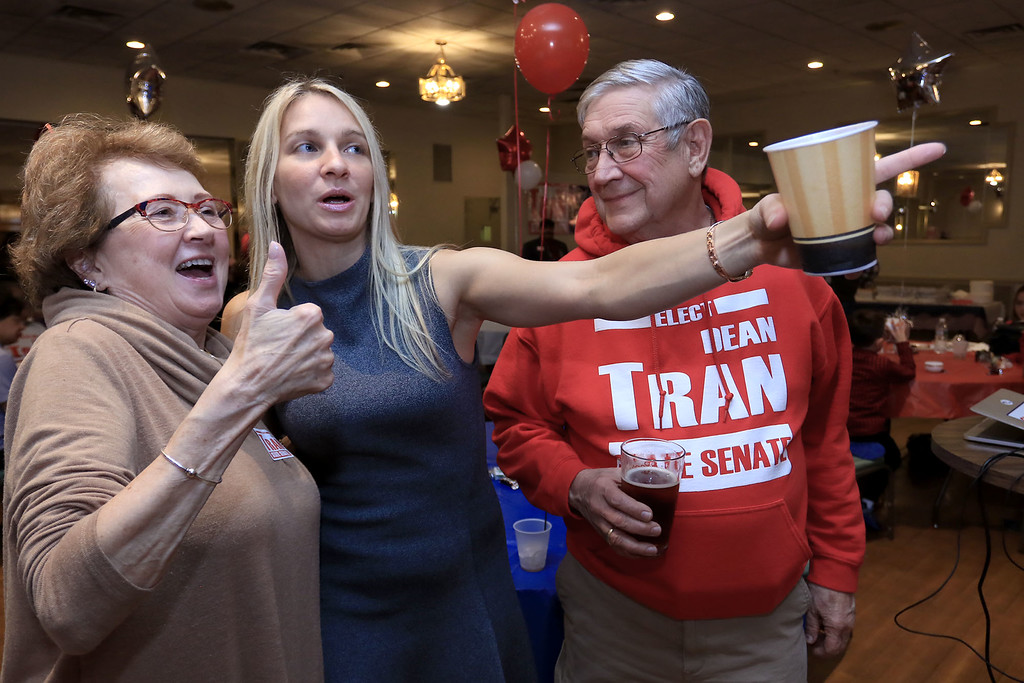 . Jane Cook of Fitchburg, Fitchburg Councilor Sam Squailia and Frank Ardinger of Leominster watch the results on a big screen at Senator Dean Tran\'s campaign party at the Leominster Elks. SENTINEL & ENTERPRISE/JOHN LOVE