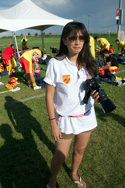 Team sports photographer covering action on the field for China ... adept with camera as well as with a lacrosse stick.