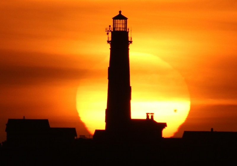 Sunset lined up with the lighthouse. The black spot on the Sun is the planet Venus!