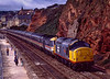 37672 piloting 43072 and 43112 with 1M62, the 08:15 Newquay - Manchester. <br /> Shown on the sea wall at Dawlish on 7th July 1990.