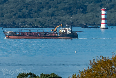 Rangitoto Lighthouse being passed by a workboat