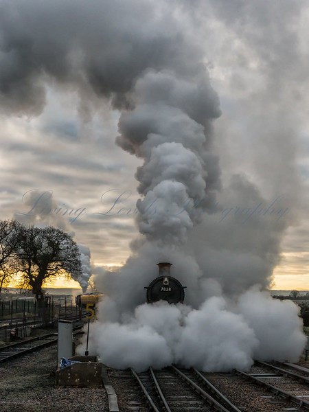 First light on a frosty morning at Bishops Lydeard station and 7828 GWR Odney Manor emerges from a cloud of steam and smoke.