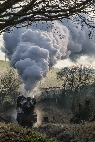 On a cold and frosty morning, 7828 GWR Odney Manor blasts out steam and smoke as it pulls the first train of the day up the bank