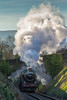 """On a cold morning, 6960 GWR Raveningham Hall blasts out steam and smoke as it pulls  the """"Cheltenahm Spa Express"""" up the bank."""