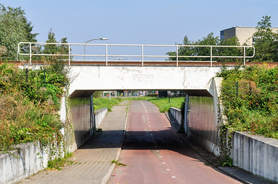 A cycle path dips below the Tilburg–Nijmegen railway in a concrete underpass in the industrial Kirkenbos neighbourhood of Nijmegen.