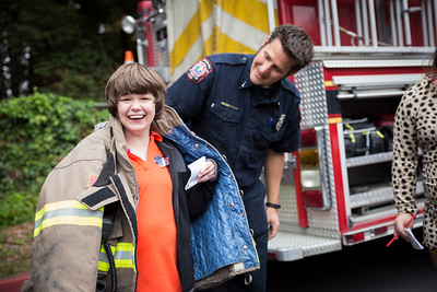 Tobi Nyles gets to try on Humboldt Bay Fire engineer Trevor Morris' fire jacket during the Glen Paul school's  transportation day.  (Sam Armanino - The Times-Standard)