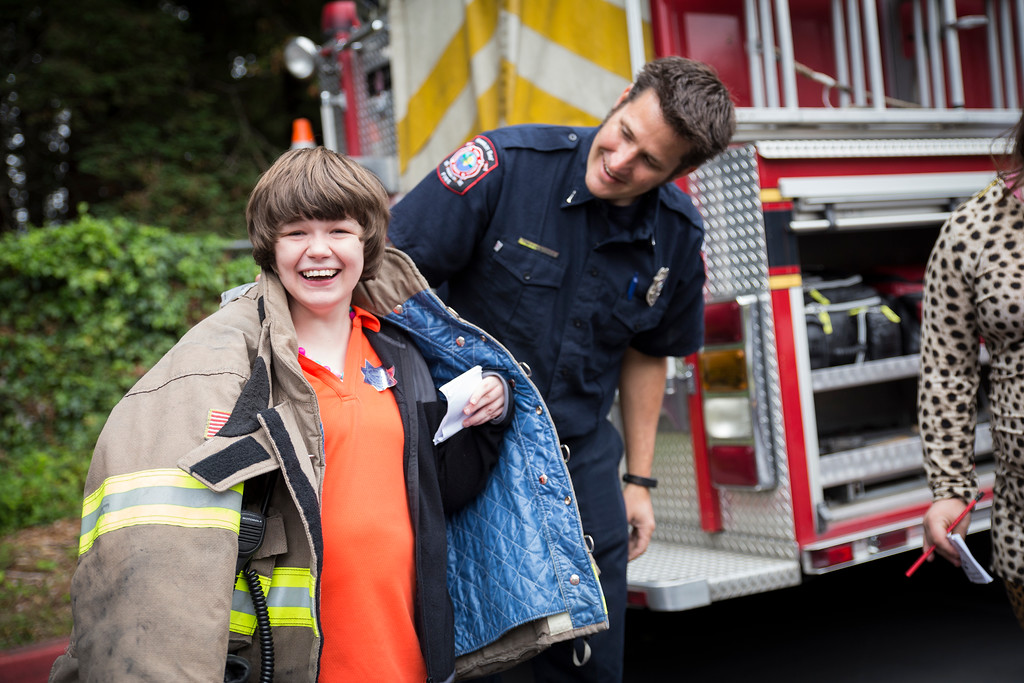 . Tobi Nyles gets to try on Humboldt Bay Fire engineer Trevor Morris\' fire jacket during the Glen Paul school\'s  transportation day.  (Sam Armanino - The Times-Standard)