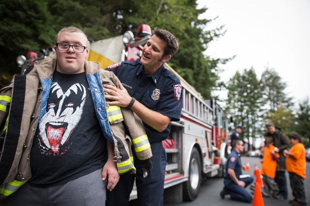 . Zachary Matlock tries on Humboldt Bay Fire engineer Trevor Morris\' jacket at Glen Paul School\'s transportation day Thursday.  (Sam Armanino - The Times-Standard)