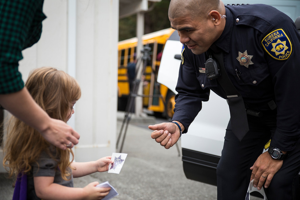 . Quinn White, 2, gets a sticker from Eureka Police Department officer Ray Nunez during Glen Paul School\'s transportation day.  (Sam Armanino - The Times-Standard)