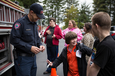 Topi Nyles gets a sticker from a Humboldt Bay Fire firefighter at Glen Paul school's transportation day on Thursday. Nine city and county vehicles were opened to Glen Paul's students. They got to see a Coast Guard boat, fire truck, ambulance, school bus, mail van, city bus, Caltrans truck during the school's Transportation Day.   (Sam Armanino - THe Times-Standard)