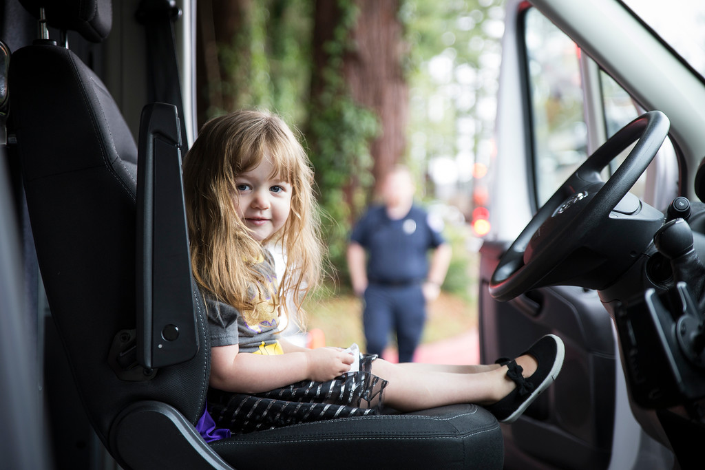. Quinn White, 2, sits in the front seat of a City Ambulance during Glen Paul School\'s transportation day.  (Sam Armanino - The Times-Standard)