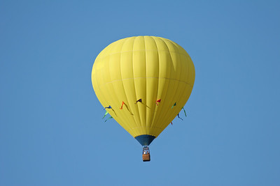 one yellow hot air balloon in the sky