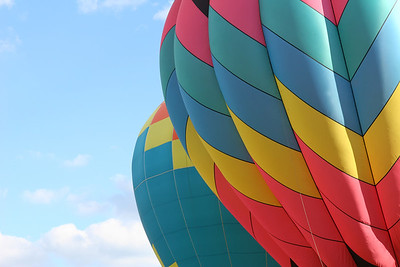 two hot air balloons up close with a blue sky in the background