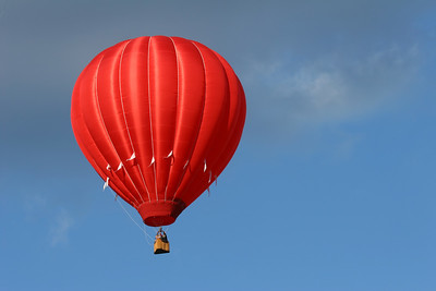 a red hot air balloon in a cloudy blue sky