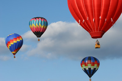 four hot air balloons flying with a cloudy blue sky