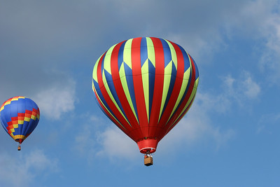 two hot air balloons flying with a cloudy blue sky