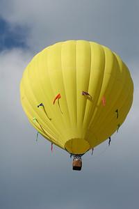 yellow hot air balloon in a cloudy blue sky