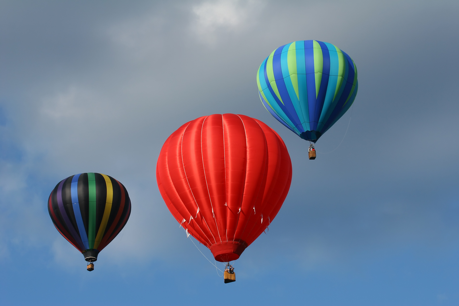 three hot air balloons in the cloudy blue sky