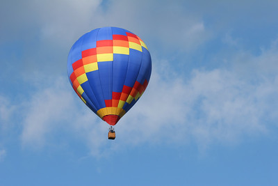 one multi colored hot air ballon with a cloudy blue sky