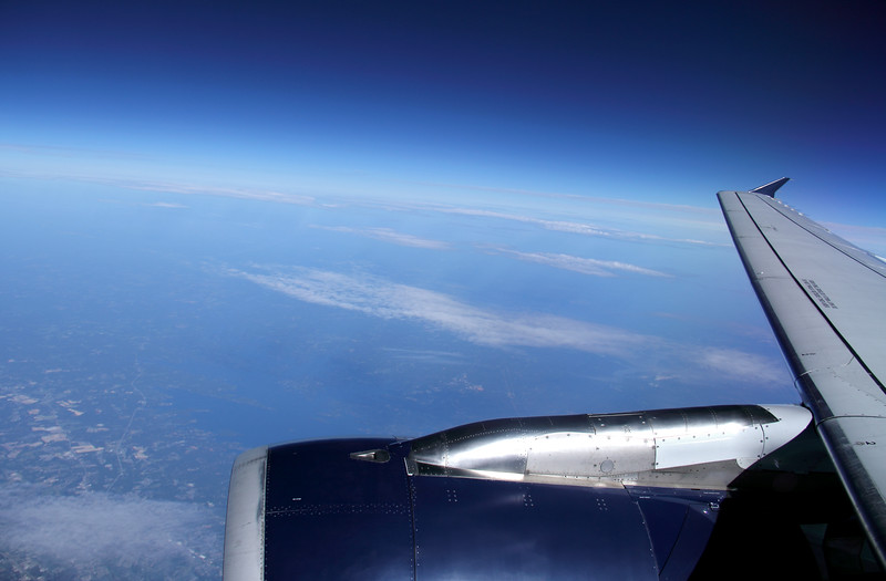 Commercial Airplane Wing in blue Sky