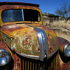 1930's Ford Dump truck sits decomposing in the desert highlands outside of a ghost town.  Yes, those are bullet holes in the windshield.