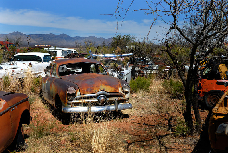 Old Ford sedan winking at the camera while rusting away in desert southwest junkyard.