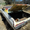 Abandoned Chevrolet coupe with trunk open.