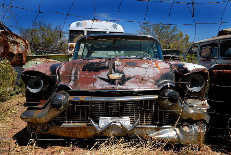 1950's Cadillac sits abandoned in desert junkyard.