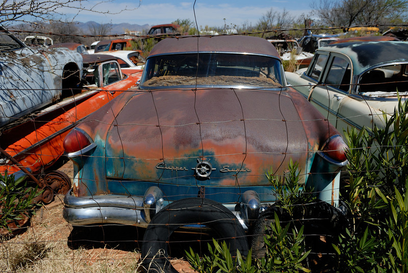 1950's Packard Clipper Super sedan sits rusting in a desert junkyard.