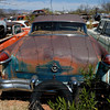 1950's Packard Clipper Super sedan sits rusting in a desert junkyard.