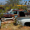 Old Ford pickup truck sits abandoned in desert junkyard.
