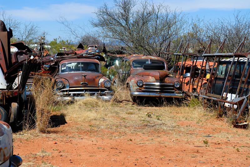2 old sedans sit together rusting in a desert junkyard.
