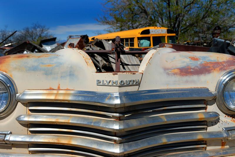 Old Plymouth sedan sits abandoned in desert junkyard.