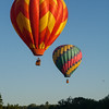 Two Hot Air Balloons Flying Over the River