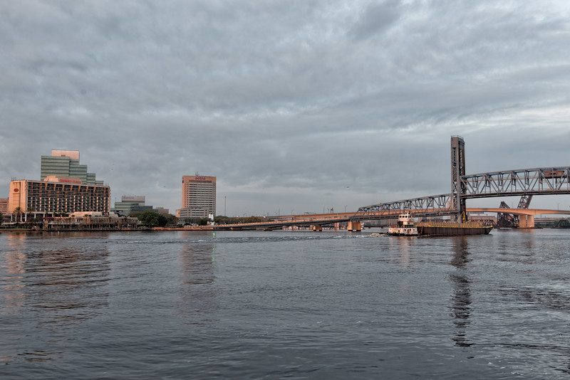 Tug and Barge steam under the Main Street Bridge
