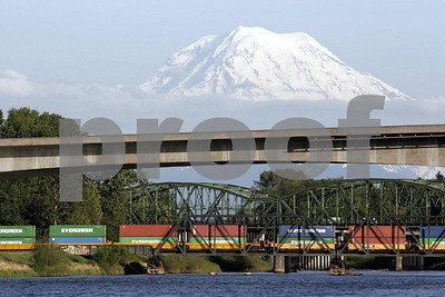 Highway and railroad bridges cross over the Puyallup River in Tacoma, Washington with Mt. Rainier in the bakcground.